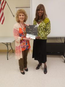 Club President, Sherry Ridge presents Dr. Constance Collins with the Book of Golden Deeds